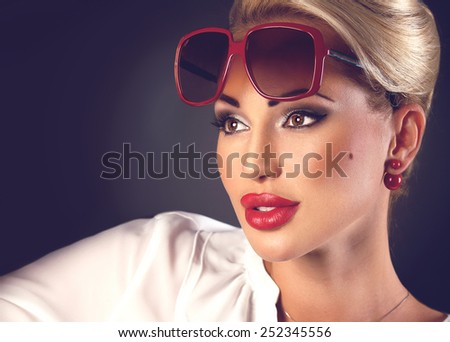 Portrait of beautiful blonde woman in sunglasses and red plump lips on dark background with copyspace - stock photo