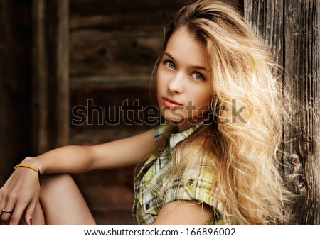 Portrait of Beautiful Blonde Woman on Wooden Background - stock photo