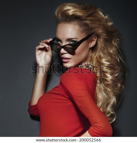 Portrait of beautiful blonde woman with long healthy curly hair. Girl posing in sunglasses - stock photo