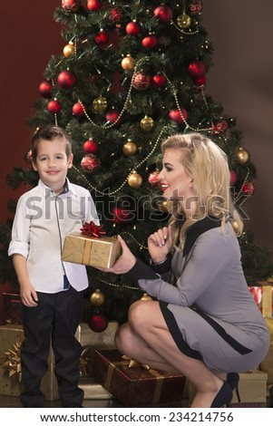Portrait of beautiful blonde young woman with her little son over christmas background  - stock photo