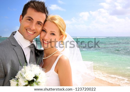 Portrait of beautiful bride and groom at the beach - stock photo