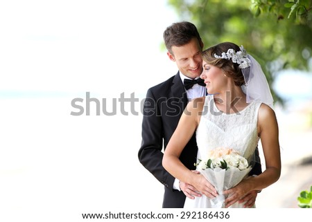 portrait of beautiful bride and handsome groom happy together with copy space - stock photo