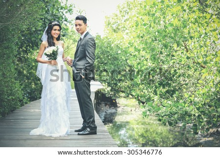 portrait of beautiful bride and handsome groom smiling and holding each other hands with copy space - stock photo