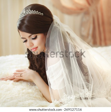 Portrait of beautiful bride with fashion veil posing on bed at wedding morning. Makeup. Brunette girl with long wavy hair styling. Wedding dress.  - stock photo