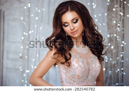 Portrait of Beautiful Brunette Bride in Lights. Fashion Dress and MakeUp - stock photo