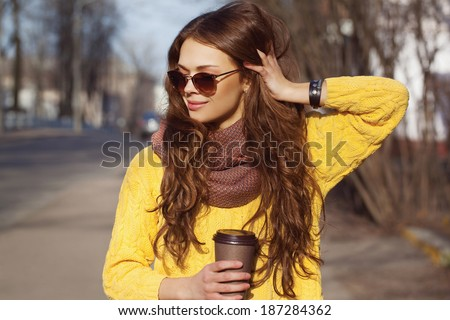 Portrait of beautiful brunette girl walking down the street. Keeping takeaway drink in one hand, other next to her head. Smiling. Urban city scene. Warm sunny weather. Outdoors - stock photo