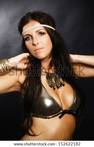 portrait of beautiful brunette in a gold bra in the studio, on a black background, glamour photography