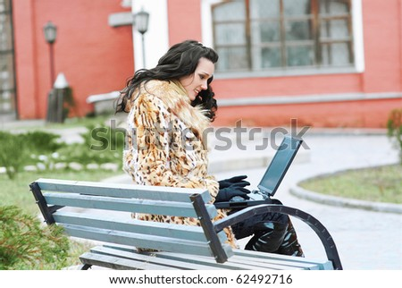 portrait of beautiful brunette in furs sitting on the bench with laptop outdoors