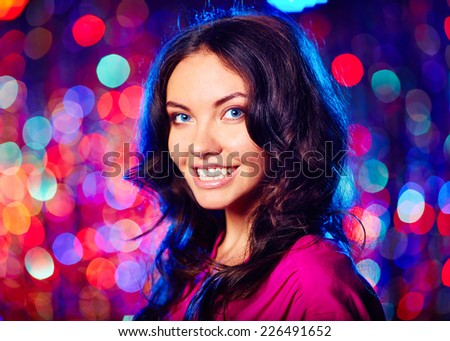 Portrait of beautiful brunette looking at camera with toothy smile over sparkling background - stock photo