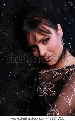 portrait of beautiful brunette on black shiny carpet - stock photo