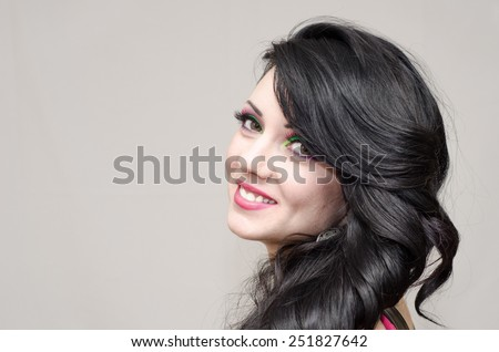 Portrait of beautiful brunette woman. Beautiful curly-haired girl with makeup. pink dress and pink lips - stock photo