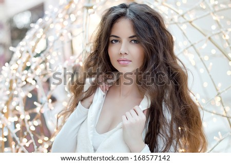Portrait of beautiful brunette woman in fashionable clothes posing blink Xmas background concept. - stock photo