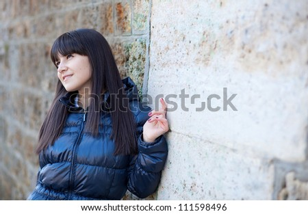 Portrait of beautiful brunette woman in front of the wall