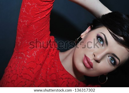 Portrait of beautiful brunette woman in red dress with evening make-up - stock photo