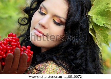 Portrait of beautiful Brunette Woman on green leaves with berry in her hands - stock photo