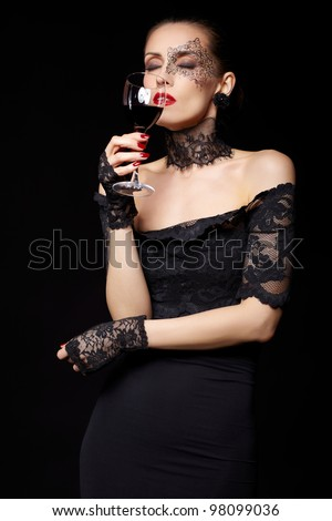 portrait of beautiful brunette woman sommelier in lacy black dress and gloves with face body art holding glass of red wine in hand with eyes shut