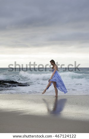 Portrait of beautiful brunette woman wearing a flowing blue dress standing by the sea with the clouds in the background