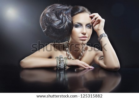 Portrait of beautiful brunette woman wearing jewellery at black mirror table - stock photo