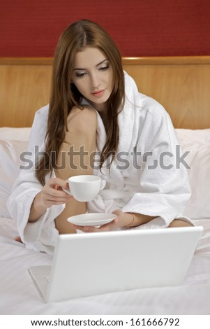 Portrait of beautiful brunette woman with laptop on bed at bedroom