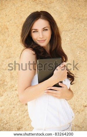 Portrait of beautiful brunette young woman holding book against beige background. - stock photo