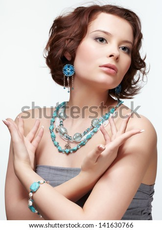 portrait of beautiful brunette young woman in blue beads, ear-rings and bracelet