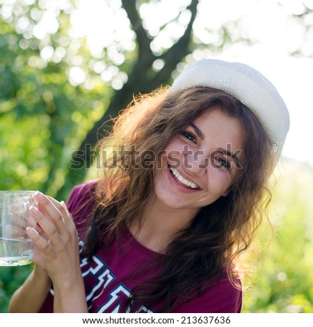 portrait of beautiful brunette young woman in white hipster hat having fun happy smiling holding glass cup of water on green summer outdoors copy space background - stock photo