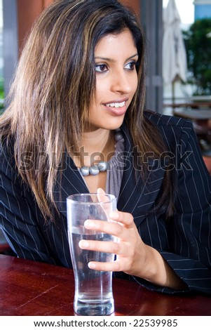 Portrait of beautiful business woman holding glass of water - stock photo