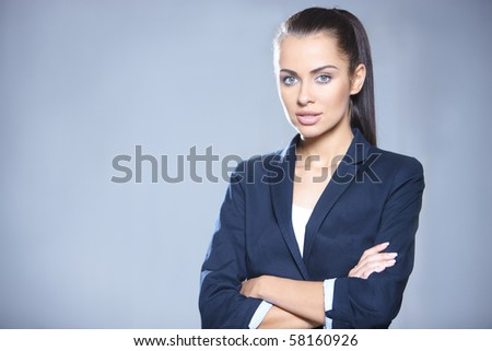 Portrait of beautiful business woman on gray background - stock photo