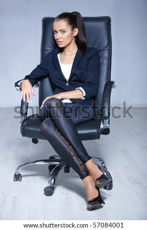 Portrait of beautiful business woman sitting on chair - stock photo