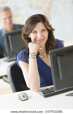 Portrait of beautiful businesswoman sitting at desk with colleague working in background - stock photo