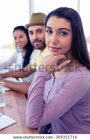 Portrait of beautiful businesswoman sitting with colleagues in conference room - stock photo