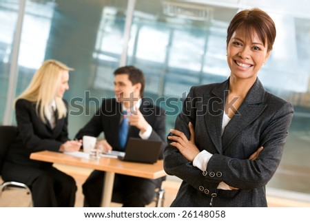 Portrait of beautiful businesswoman standing at foreground of communicating co-workers - stock photo