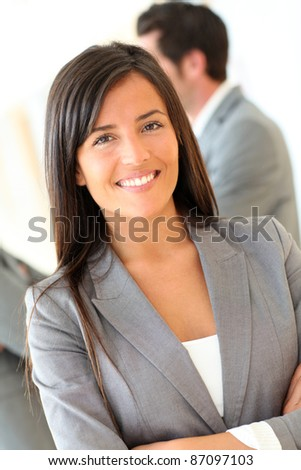 Portrait of beautiful businesswoman standing in front of group