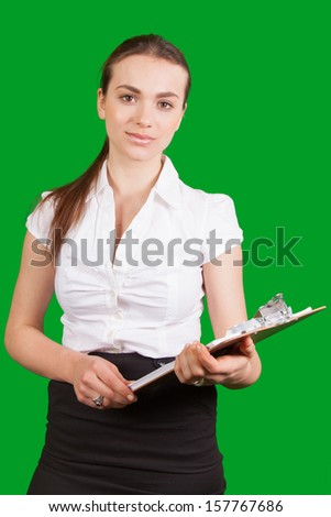 Portrait of beautiful businesswoman with clipboard looking at camera with green background - stock photo