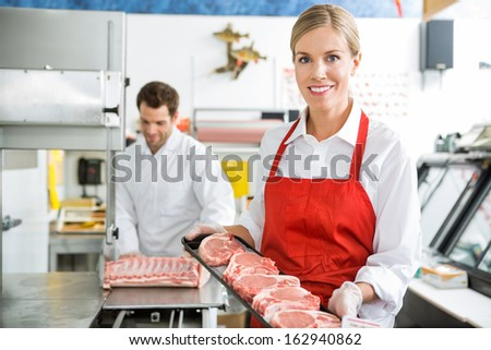 Portrait of beautiful butcher holding meat tray at store with colleague working in background