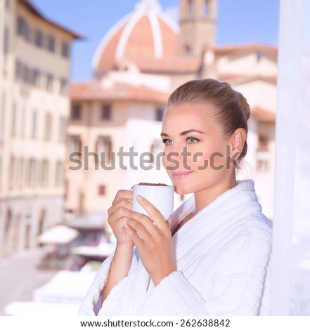 Portrait of beautiful calm woman drinking coffee in hotel room in Florence, Italy, Europe, standing on balcony on wonderful cityscape background - stock photo