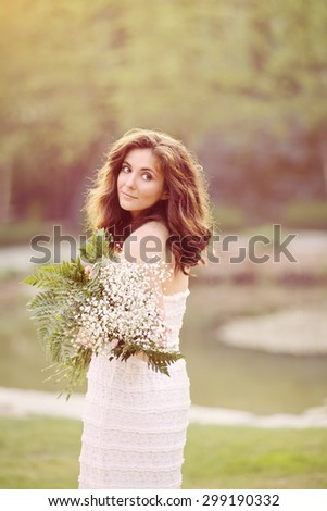 Portrait of beautiful Caucasian adult girl woman with long dark brown hair in white summer open dress in park outside with white flowers in hands on sunset, toned with Instagram filters, soft pastel - stock photo