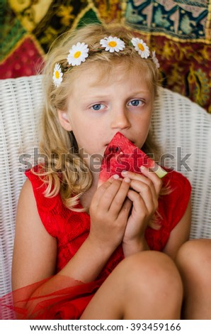 portrait of beautiful caucasian blond girl sitting and eating watermelon - stock photo