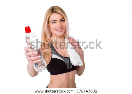 Portrait of beautiful caucasian blonde sporty woman. Young athlete smiling, holding bottle of water, looking at camera. Isolated on white background - stock photo