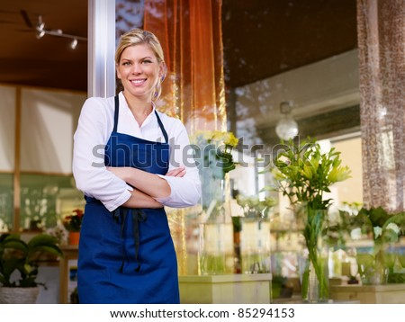 Portrait of beautiful caucasian girl self-employed in flower shop, smiling and looking at camera. Horizontal shape, waist up