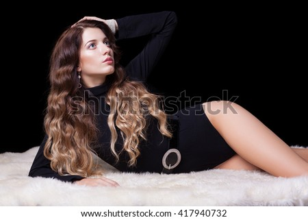Portrait of beautiful caucasian model posing on white furs in body on black background