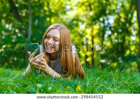 Portrait of beautiful caucasian smiling red-haired young woman, against summer green park.