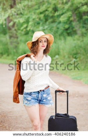 Portrait of beautiful Caucasian young girl in white sweater, blue denim shorts, straw hat, standing with travel bag on the wild country road in forest looking in camera, wanderlust adventure vacation  - stock photo
