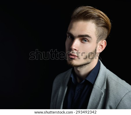 Portrait of beautiful charming young man with blue eyes and fair hair over black background - stock photo