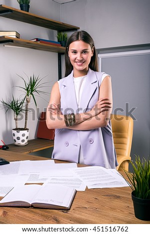 Portrait of beautiful cheerful businesswoman with arms crossed at table with documents - stock photo