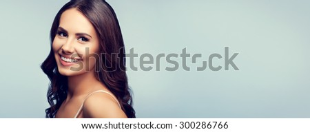 Portrait of beautiful cheerful smiling woman in white tank top clothing, with blank copyspace area for text or slogan - stock photo