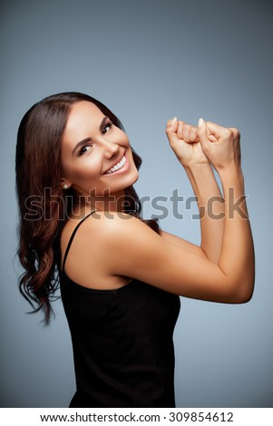 Portrait of beautiful cheerful smiling young woman happy gesturing, over grey background - stock photo