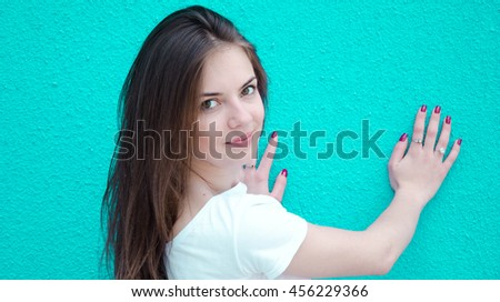 Portrait of beautiful cheerful smiling young woman, on blue background - stock photo