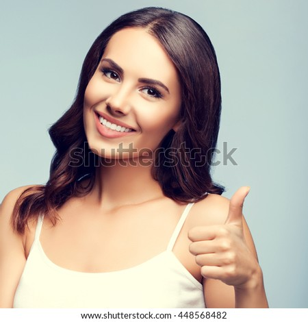 Portrait of beautiful cheerful smiling young woman showing thumb up gesture - stock photo