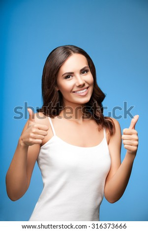 Portrait of beautiful cheerful smiling young woman showing thumb up gesture, on blue background - stock photo